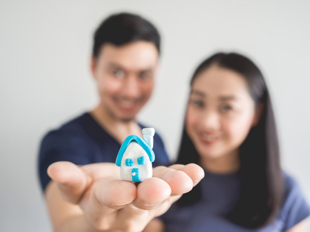 Happy couple lover showing small house in hand. Concept of buying house to start a family.