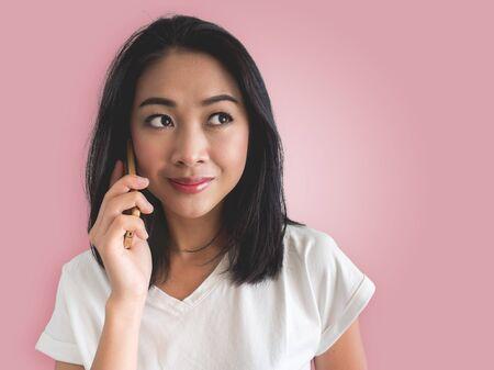 アジアの女性の笑顔は、彼女のスマート フォンの電話です。 写真素材