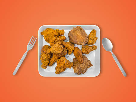 Fried chicken on white plate served on table. Concept of eating a lot. Stock Photo