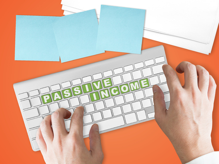 Concept of passive income business trend. Passive Income words on green keyboard buttons.