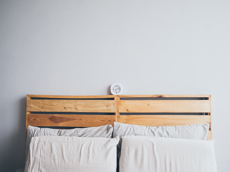 daily room: White simple clock on loft woden bed in the morning.