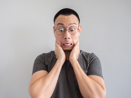Shocked and surprised freelance Asian man with funny face.