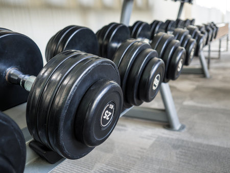 Dumbells set left on the racks in the gym. Reklamní fotografie - 81264183