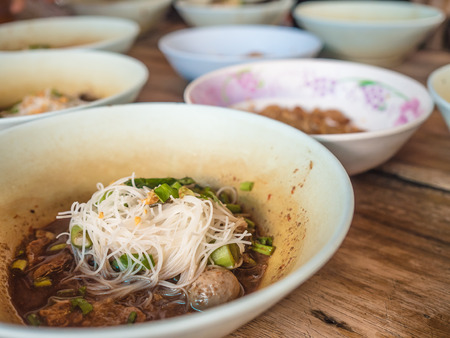 favorite soup: Many small bowls Thai noodle served on table. Stock Photo
