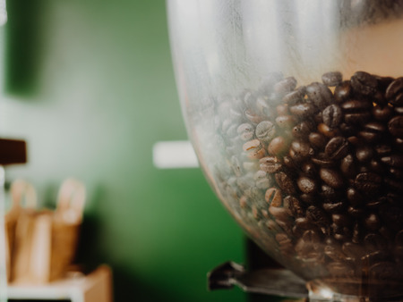Close up of coffee beans in the machine with green wall as background.