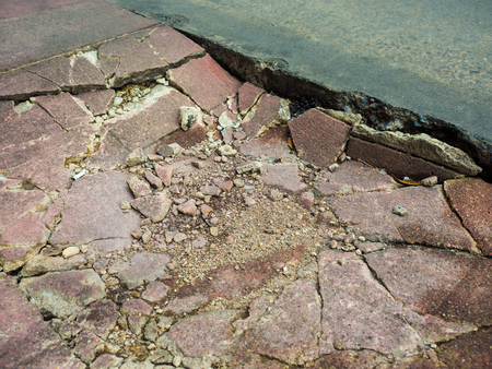 Cracked and damaged cements footpath. Stock Photo