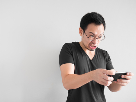 Angry Asian man is losing the mobile game.