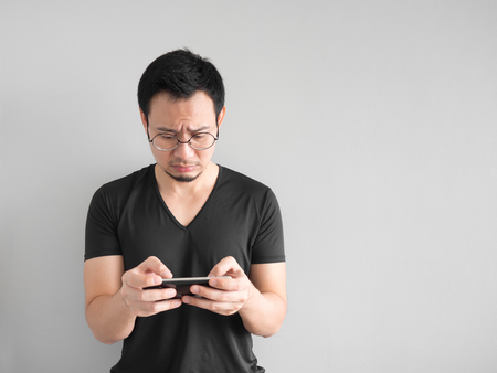 he: Sad Asian man lost the game he played in the smartphone. Stock Photo