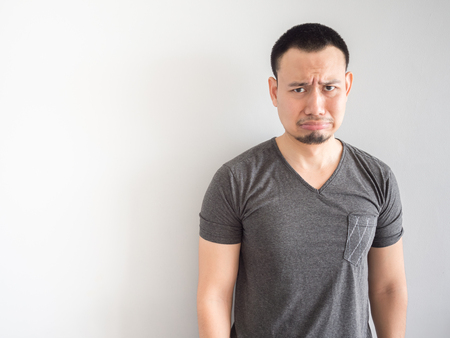 Sad and scared expression face of asian man in black t-shirt.