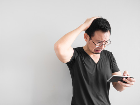 Sad Asian man lost the game he played in the smartphone. Stok Fotoğraf