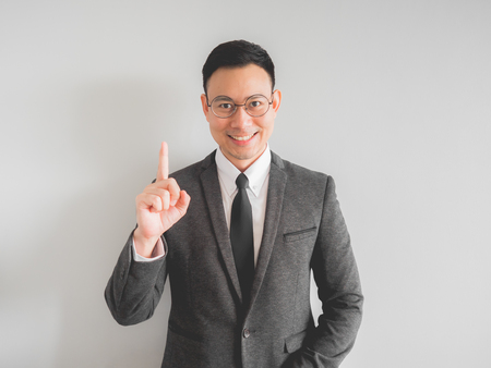 Happy Asian boss manager business man wears black suit in relax pose.