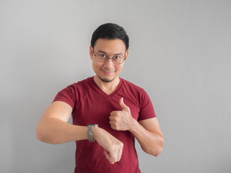 Happy and surprised Asian man who is looking at his watch. Archivio Fotografico