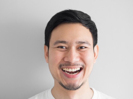 Head shot of laughing face Asian man.