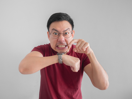 frustrated and angry Asian man who waiting for a friend who late for an appointment. Stock Photo