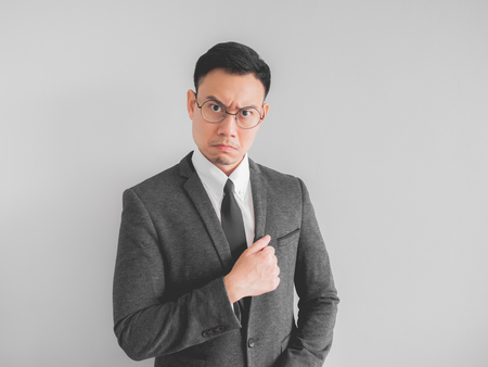Angry Asian boss manager businessman in black suite.