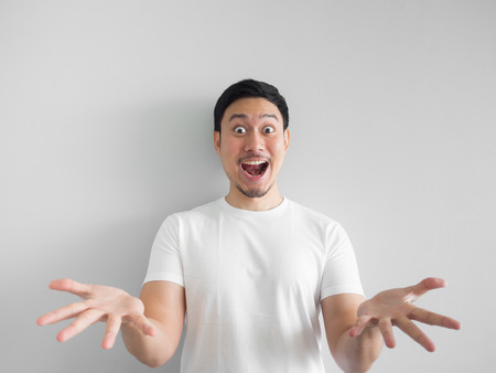 Surprised face of happy asian man in white shirt  light grey background. Archivio Fotografico