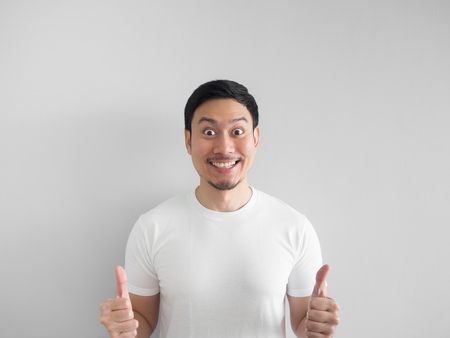Surprised face of happy asian man in white shirt  light grey background. Standard-Bild