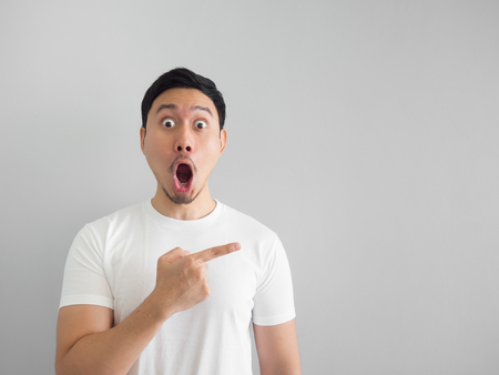 Shocked face of Asian man in white shirt on grey background.