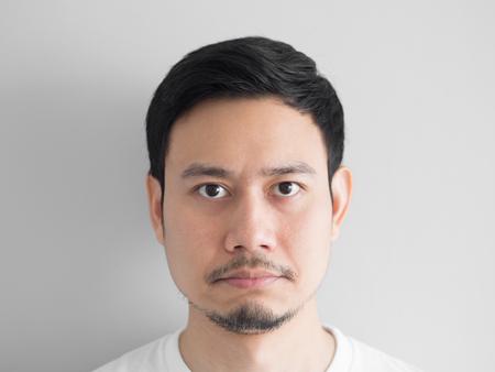 Hoofd geschoten van chagrijnig gezicht Aziatische man.