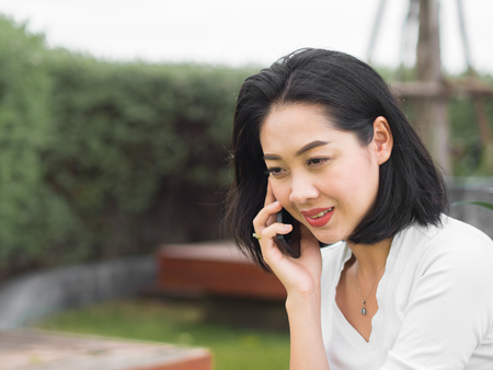 Happy Asian woman got good news on the phone.