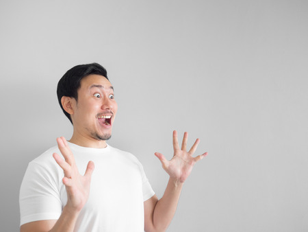 Surprised face of happy asian man in white shirt  light grey background. 스톡 콘텐츠
