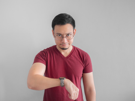 Angry and unpleasant face of Asian man is looking at his watch waiting for someone.