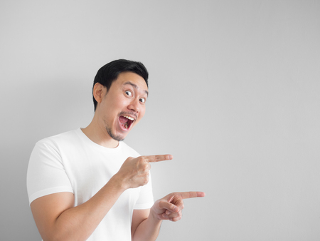 Surprised face of happy asian man in white shirt  light grey background. Banque d'images