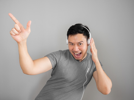 Happy Asian man listens to music and funny dance.