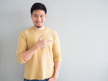 Asian man in yellow t-shirt excited to point and present an empty space background.