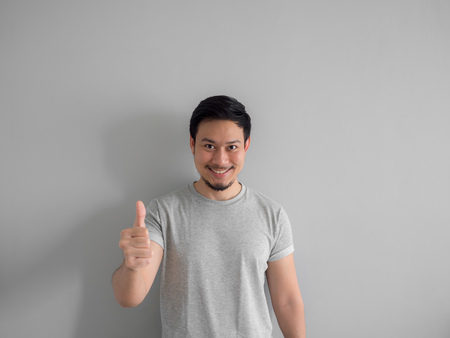 Happy face of Asian man with beard in grey t-shirt. 스톡 콘텐츠