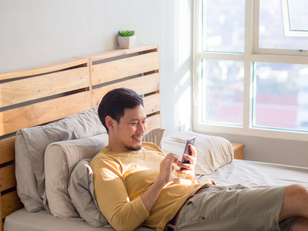Asian man using smartphone in his bed in the morning. Stock fotó