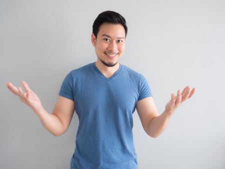 Smile and happy Asian man in blue t-shirt and grey background. 版權商用圖片