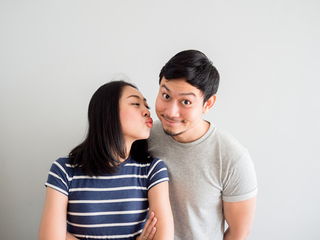 Funny lovely Asian couple trying to kiss each other. Concept of comedy love.