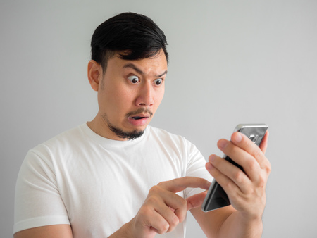 Shocked and scary face of Asian man get yelled from smartphone. See something scary in smartphone.