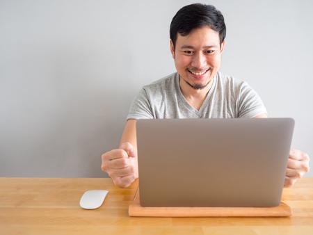 笑顔アジアの男は、ラップトップで彼の仕事に満足感を感じています。 写真素材 - 96676815