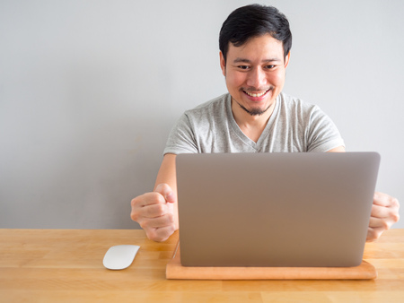 Smile Asian man is feeling happy with his work in the laptop.