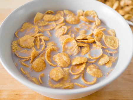 Cornflakes cereal breakfast on wooden table.