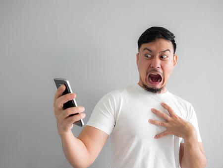 Entsetztes und beängstigendes Gesicht des asiatischen Mannes erhalten vom Smartphone geschrien. Sehen Sie etwas Beängstigendes im Smartphone. Standard-Bild
