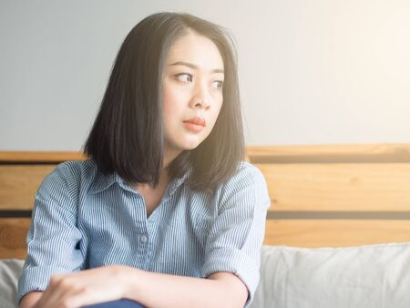 Asian woman sits on her bed in  day time. Stock Photo