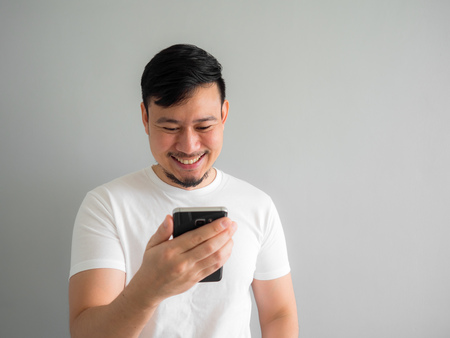 Funny laugh face of Asian man watching funny video clip share in social in the smartphone. 写真素材