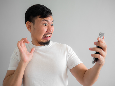 Shocked and scary face of Asian man get yelled from smartphone.  See something scary in smartphone. Stockfoto