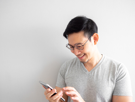 Happy Asian man is using smartphone. Concept of using social media on mobile phone.