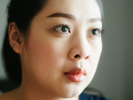 Close up face of Asian woman in normal emotion with low light from window. Stock Photo