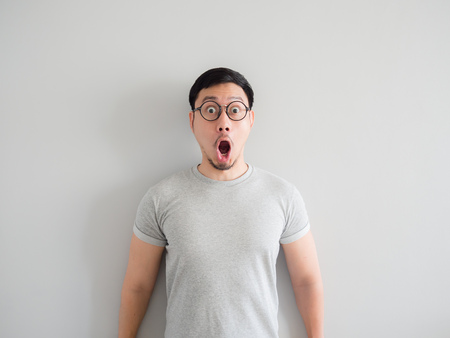 Amazing and shocked face of Asian man with eyeglasses. Stock Photo