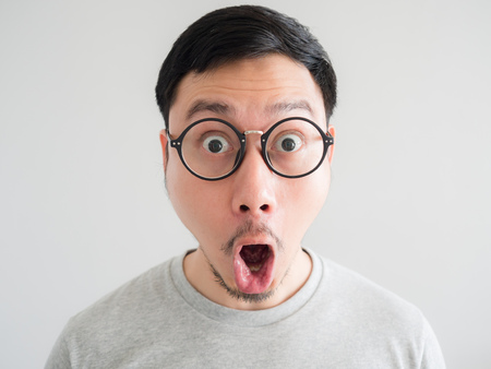 Amazing and shocked face of Asian man with eyeglasses. Фото со стока