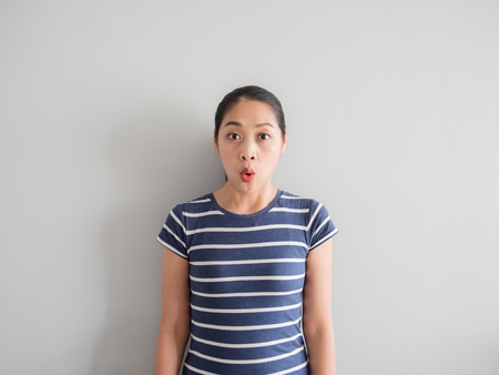Shocked and amazing face of Asian woman on grey background. Archivio Fotografico