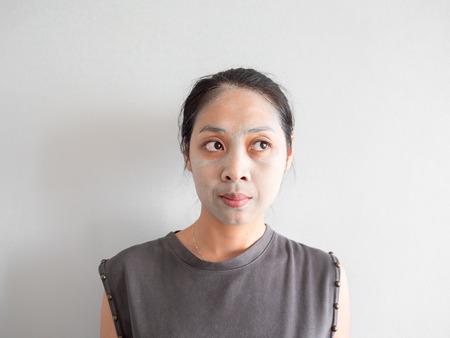 Unprofessional Asian housewife woman applying green facial clay mask.