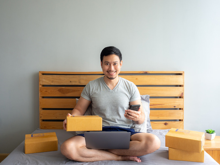 Happy Asian man success on making his online store. Concept of freelance startup and online business home office.