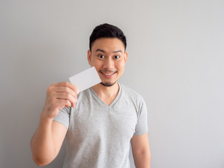 Happy Asian man is showing a white credit card.