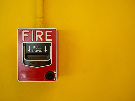 Red manual fire alarm activation switch mounted on yellow wall.